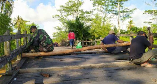 Personel Koramil 1011-12/Kahayan Kuala Memperbaiki Jembatan Bersama Warga